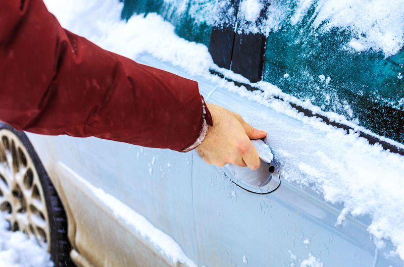Cropped hand of woman holding vehicle door during winter