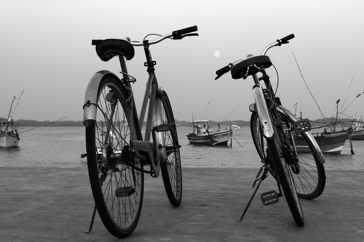 Bicycles parked at beach against sky
