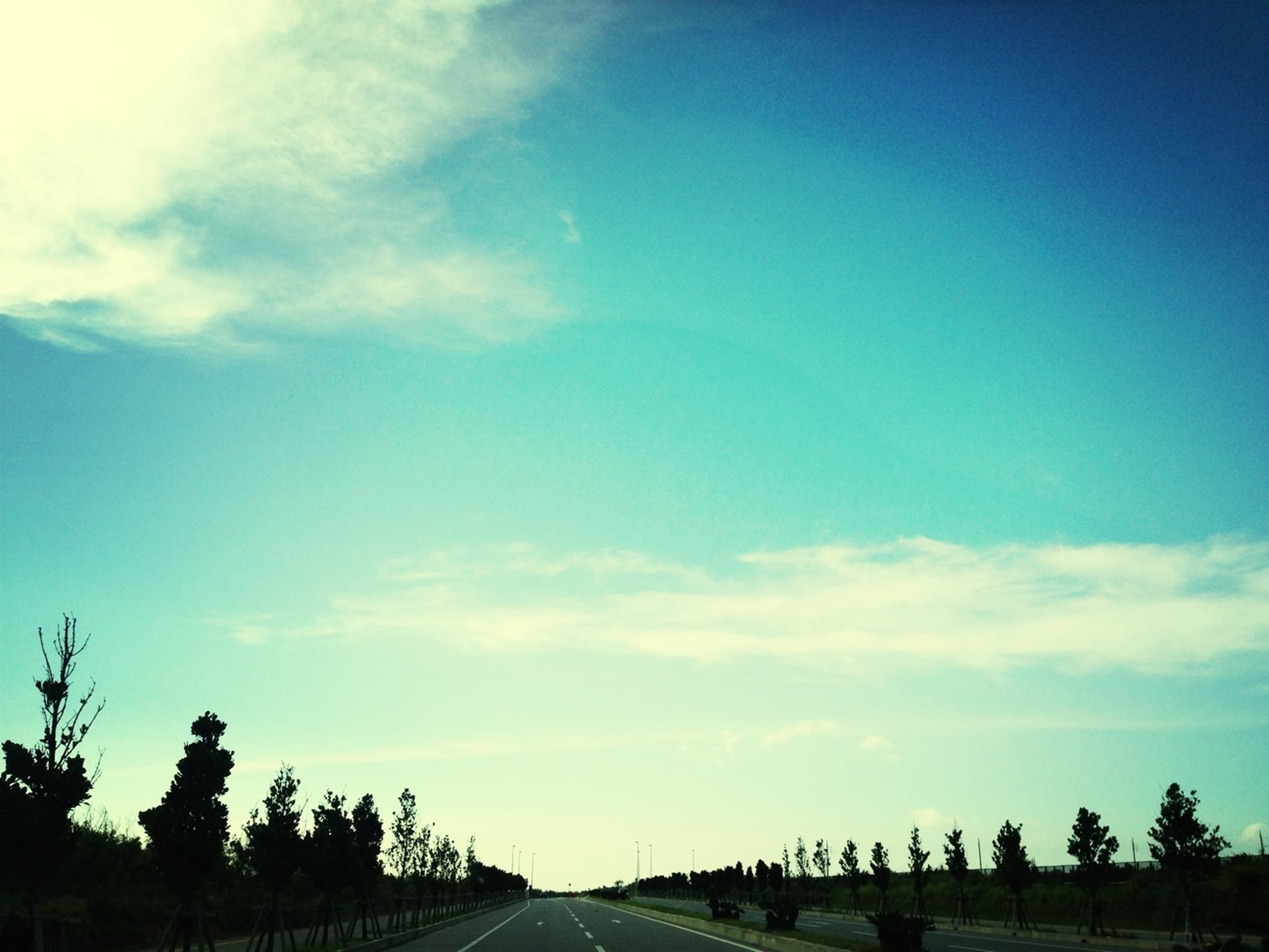 sky, the way forward, road, tree, diminishing perspective, transportation, vanishing point, tranquility, cloud - sky, tranquil scene, blue, nature, cloud, landscape, scenics, beauty in nature, outdoors, silhouette, growth, long