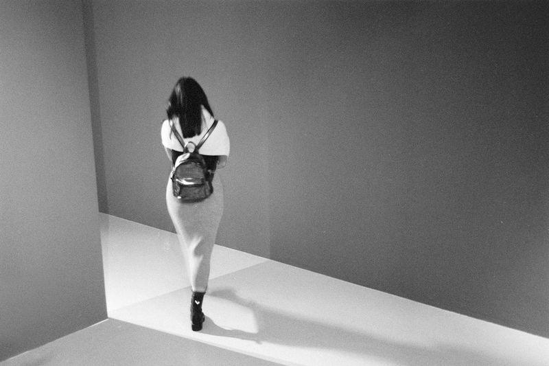 Rear view of woman walking in a museum hallway