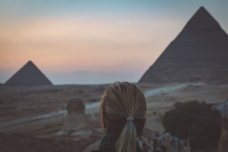 Sky Nature Outdoors Pyramids Egypt Desert Travel Tourism Destination Beautiful Ancient Structure Ruins Giza Cairo Sphinx Architecture Pyramid Built Structure Travel Destinations Sunset History The Past People Focus On Foreground Building Exterior Ancient Civilization Real People Rear View Hairstyle Climate It's About The Journey 2018 In One Photograph