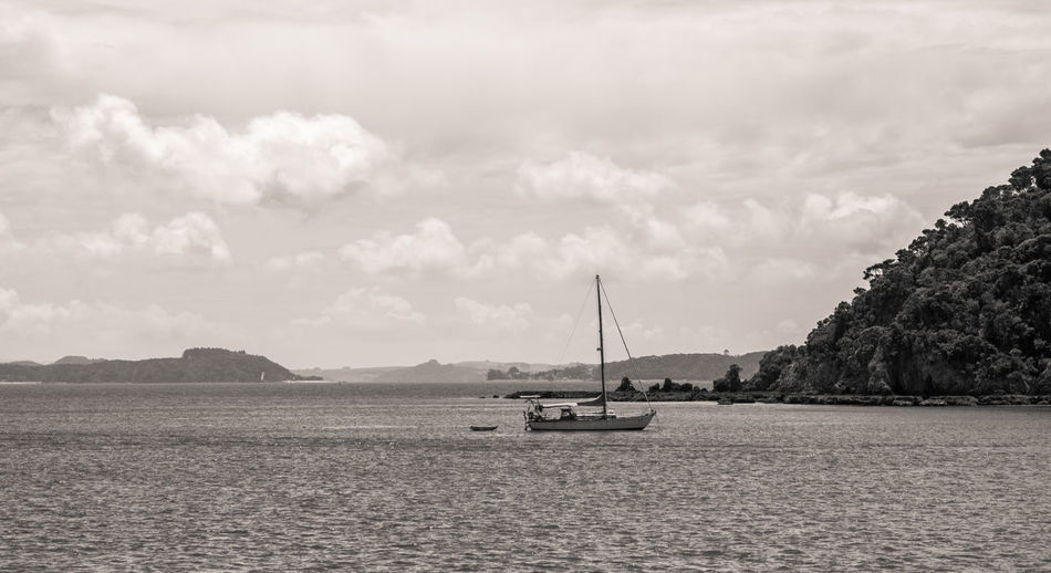 Boats in sea against cloudy sky