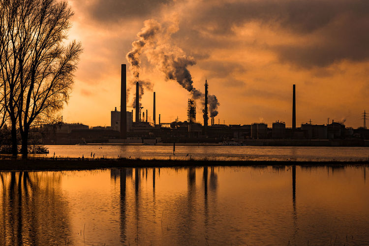 #rhinegrasslandskasslerfeld03 Duisburg Rhein Air Pollution Architecture Building Exterior Built Structure Chimney Cloud - Sky Emitting Factory Industry Nature No People Outdoors Pollution Reflection River Sky Smoke - Physical Structure Smoke Stack Sunset Tree Water Waterfront