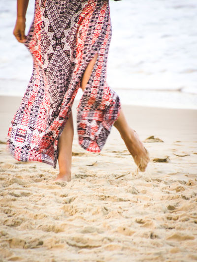 Low Section Of Woman Walking On Sand At Beach