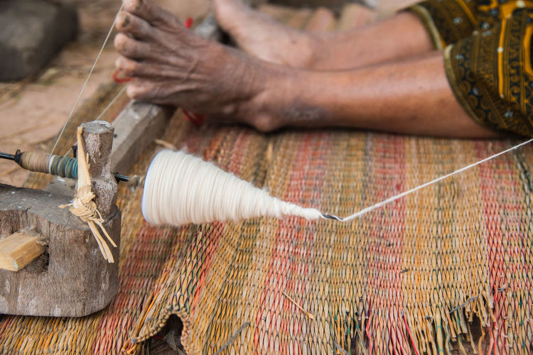 Low section of person weaving loom on mat