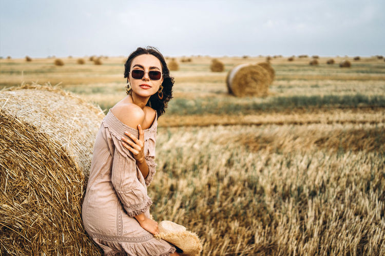 Portrait of young woman with hay bales on field