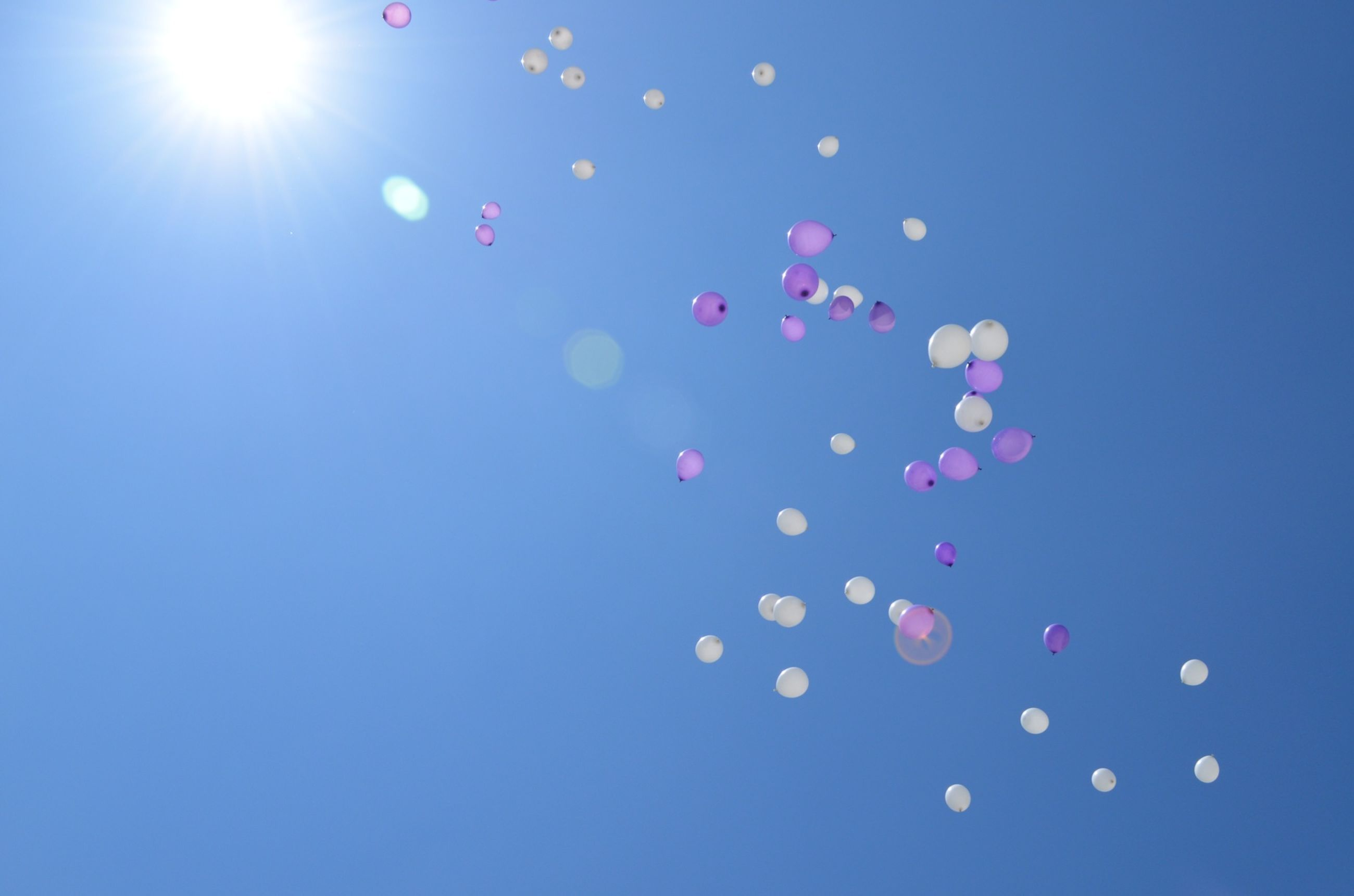 low angle view, sun, blue, lens flare, clear sky, sunlight, sunbeam, multi colored, bright, sunny, copy space, sky, balloon, outdoors, day, mid-air, no people, nature, beauty in nature, tranquility