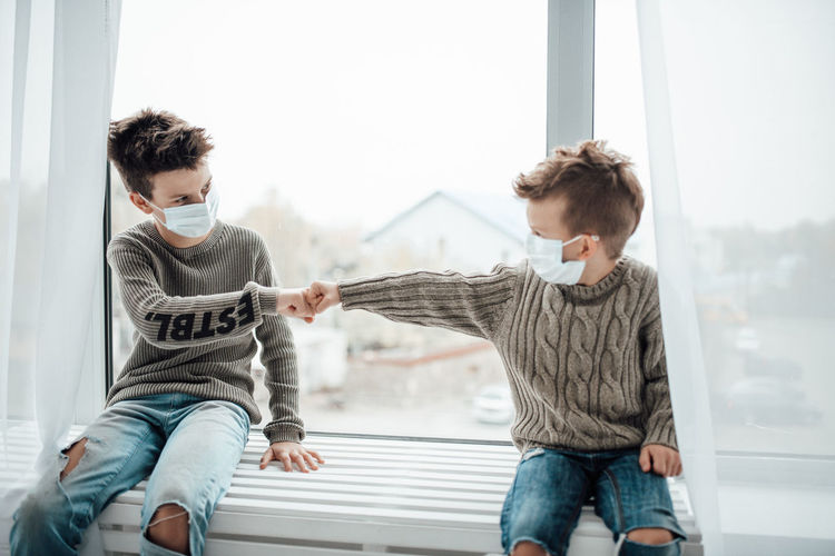 Brothers wearing mask doing fist bump sitting by window at home