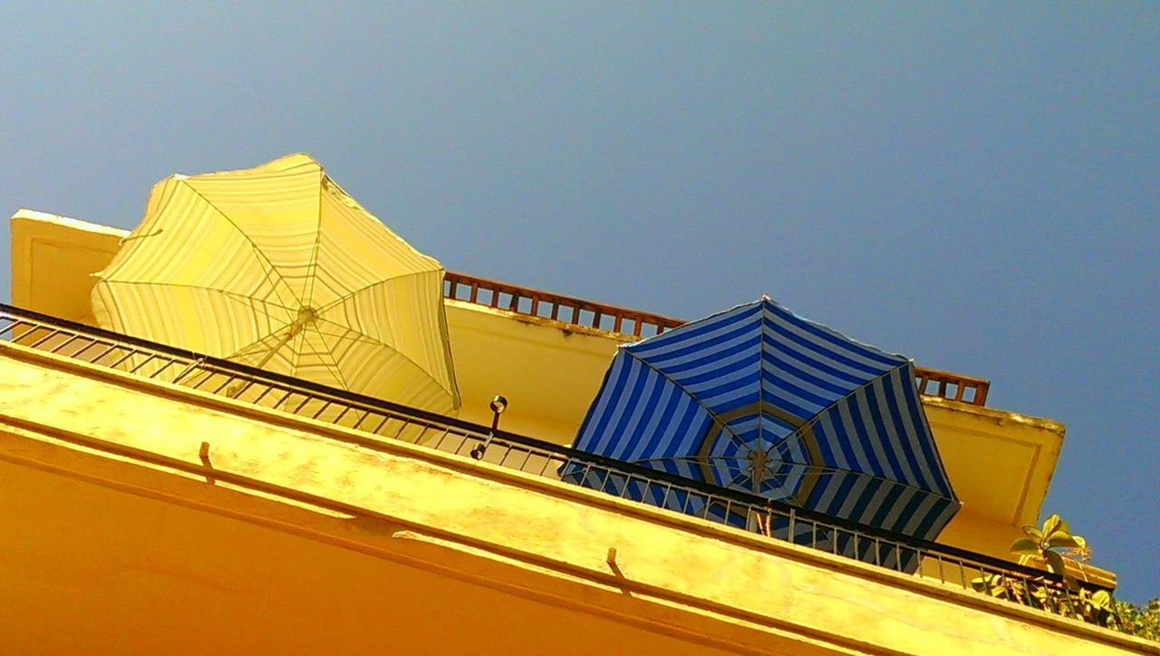 Low angle view of sun umbrellas on balcony