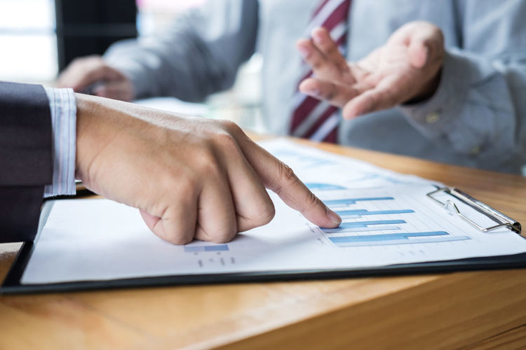 Cropped Image Of Business People Working Over Graph In Office