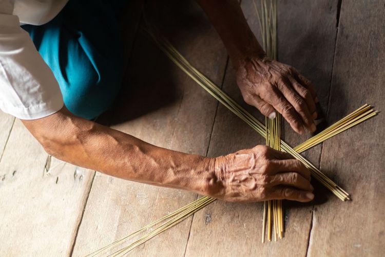 Cropped hands adjusting sticks on wooden floor