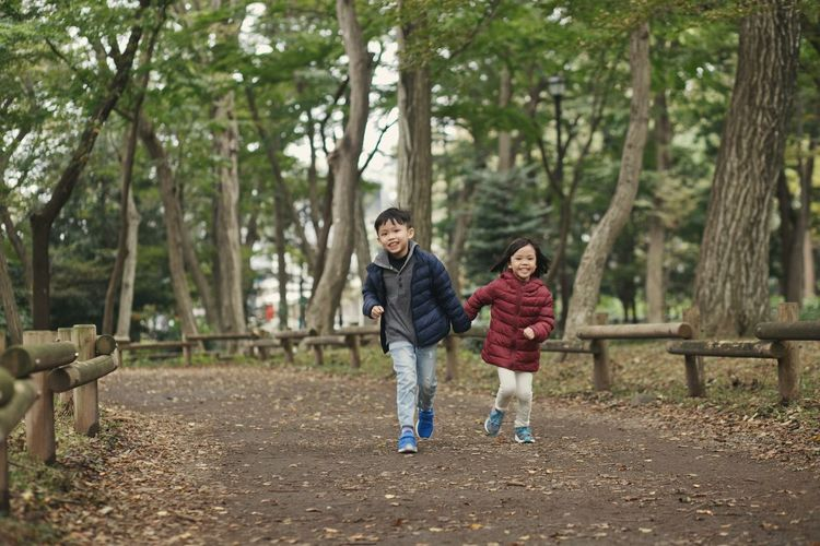 siblings running at the park Outdoors Siblings Happy Playground Park Springtime Asian  Girl Cute Boy Portrait Tree Young Women Friendship Child Togetherness Sports Clothing Full Length Exercising Healthy Lifestyle Childhood Playground Running Jogging