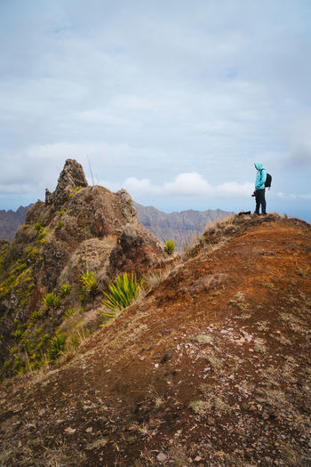 Traveler with backpack looking over the mountain peaks. Stunning arid landscape of Santo Antao island, Cabo Verde. Cape Verde Activity Adventure Beauty In Nature Cloud - Sky Day Full Length Leisure Activity Lifestyles Men Mountain Mountain Range Nature One Person Outdoors Real People Rock Rock - Object Santo Antao Scenics - Nature Sky Solid Standing Stillness In Time Tranquility