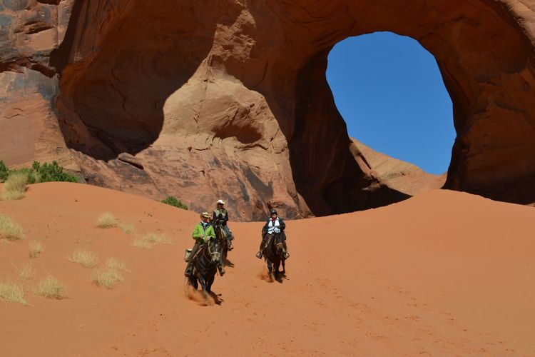 People Riding Horses At Desert