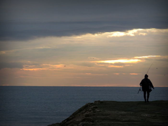 Silhouette of man with fishing rod against sea