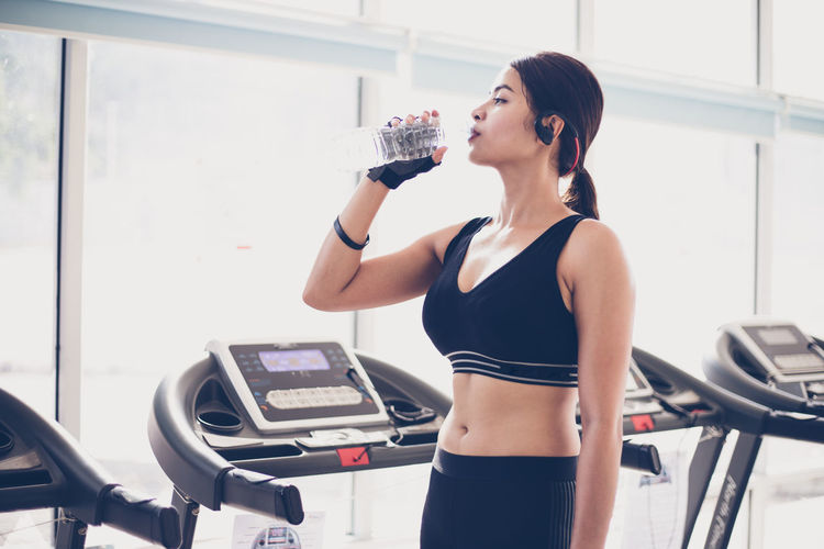 Young Woman Drinking Water While Standing In Gym