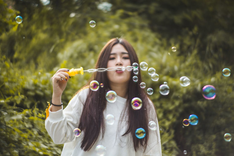 Young woman blowing bubbles against plants