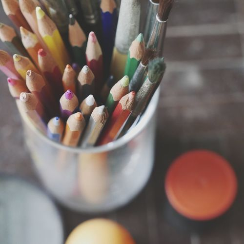 High Angle View Of Colored Pencils And Paintbrushes In Container