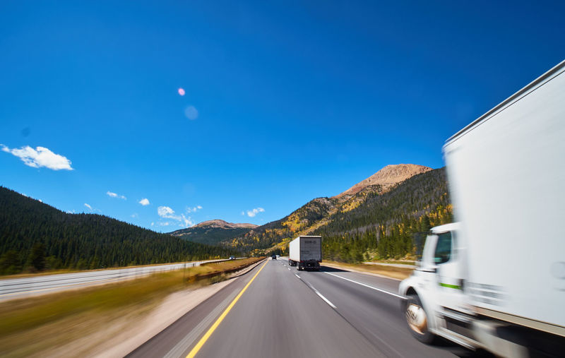 Transportation Road Sky Land Vehicle Motion Mode Of Transportation Mountain The Way Forward Nature Motor Vehicle on the move Blurred Motion Truck No People Direction Speed Car Semi-truck Road Marking Highway Outdoors Road Trip Multiple Lane Highway