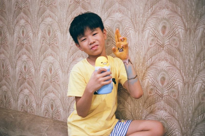 Full length of boy holding toy against wall