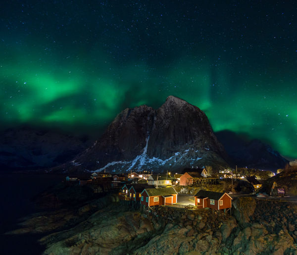 Illuminated houses by mountain against aurora borealis in sky at night
