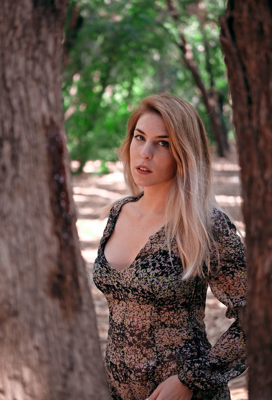 young adult, young women, tree, one person, real people, beautiful woman, leisure activity, tree trunk, looking at camera, lifestyles, portrait, outdoors, nature, standing, beauty, day
