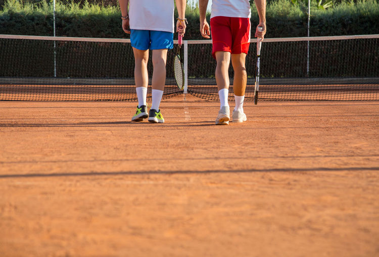 Low section of male friends playing tennis on court
