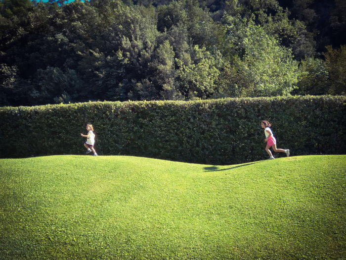 Sisters Running On Field Against Trees