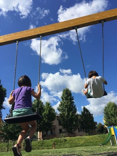 Children swinging at playground against sky