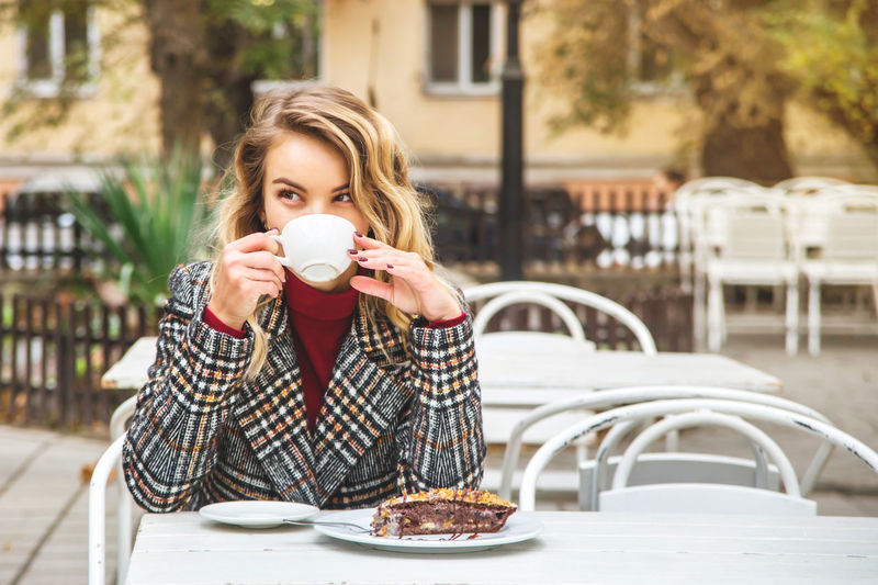Thoughtful young woman having dessert with coffee at outdoor cafe