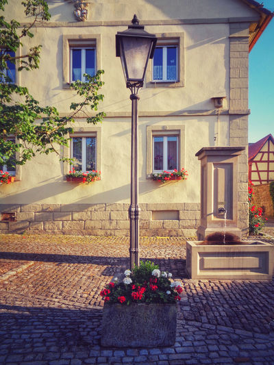 Franconian village feeling -- It's warm, it's summer and the mood is great. Like this scene nearly every franconian village spreads its charme and warm feelings. Franconia Village Abtswind Lamp Lamp Post Fountain Architecture House Façade Traditonal Windows City Village Life Life Daily Life Cobblestone Flowers Summer Sun Heat War Summer Feeling Relaxing Still Life Scene Scenery Steigerwald Bavaria Germany German Sightseeing Hiking Building Exterior Built Structure Building Window Flower Flowering Plant Plant Residential District Nature Potted Plant No People Street Lighting Equipment Outdoors Day Footpath Sidewalk Flower Pot Flower Arrangement Bouquet Electric Lamp Houseplant