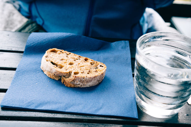 Close-up of brown bread and water in glass on table