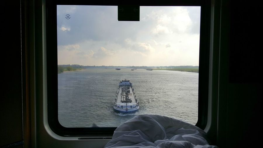 Barge seen through ship window on river