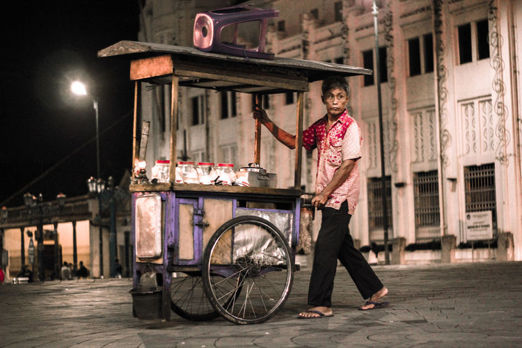 Full length of vendor pushing concession stand on street in city at night