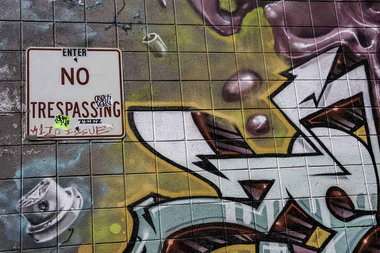 No trespassing sign with stickers and written comments next to graffiti in an alley. Alley Building Exterior Communication Flouting The Rules No People No Trespassing Sign Resist Rules Sign Street Art Streetphotography Text Graphic