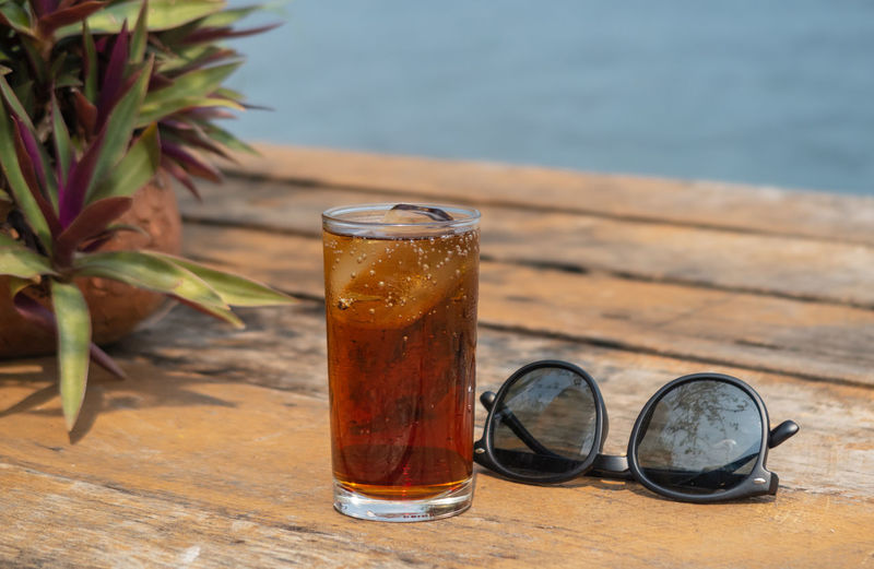 Close-up of cold drink by sunglasses on table outdoors