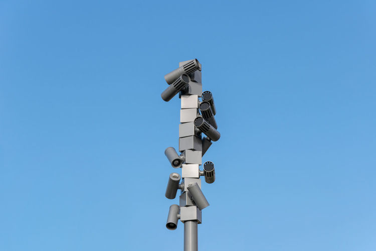 Low angle view of security cameras against clear blue sky
