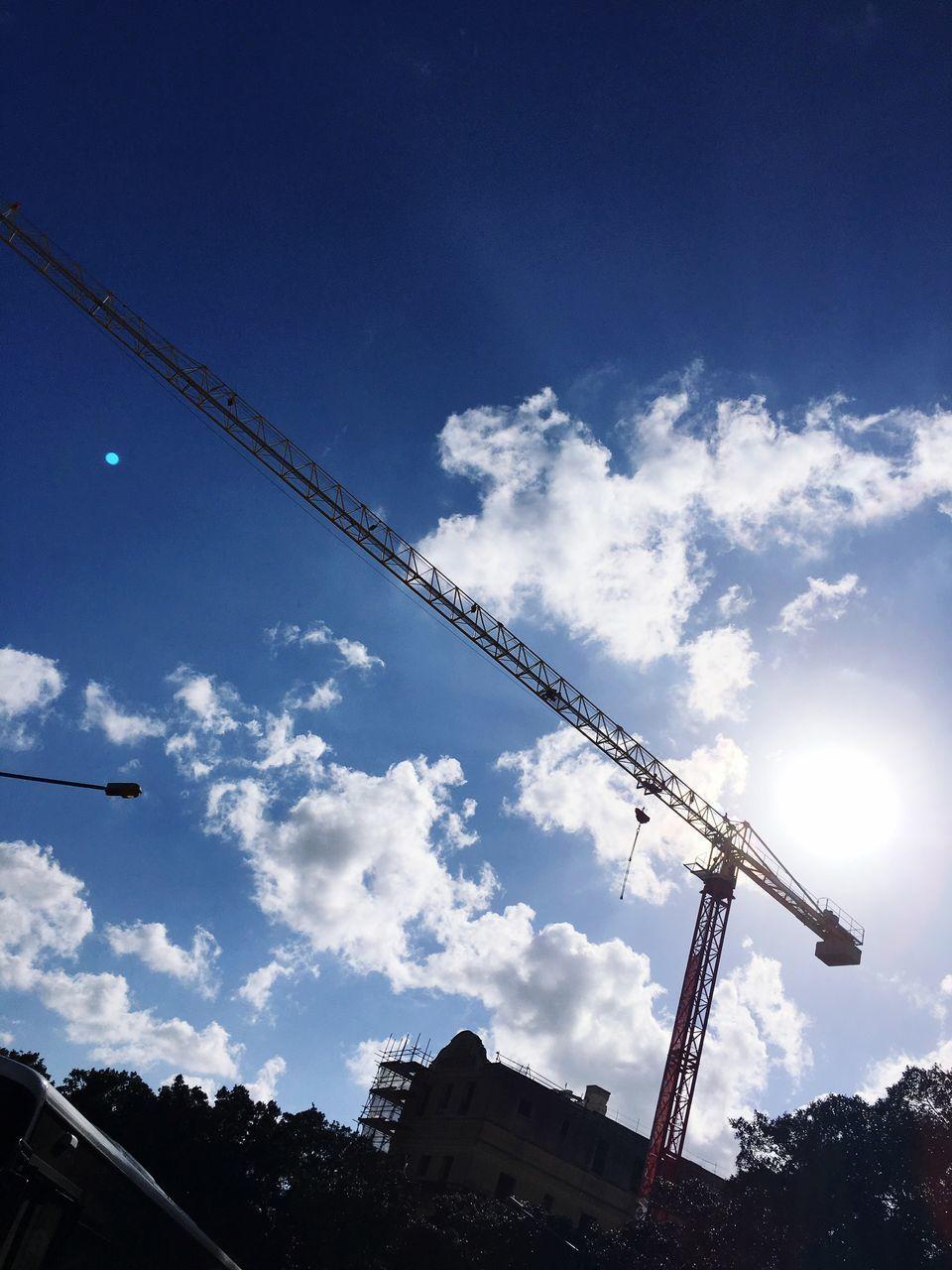 crane - construction machinery, sky, low angle view, construction site, built structure, development, architecture, cloud - sky, crane, building exterior, silhouette, construction industry, construction, industry, tall - high, cloud, dusk, outdoors, incomplete, blue