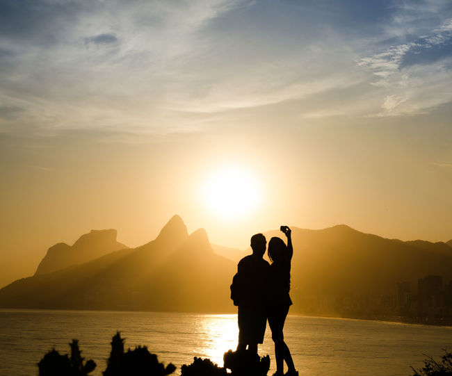 Silhouette couple taking selfie by sea against sky during sunset
