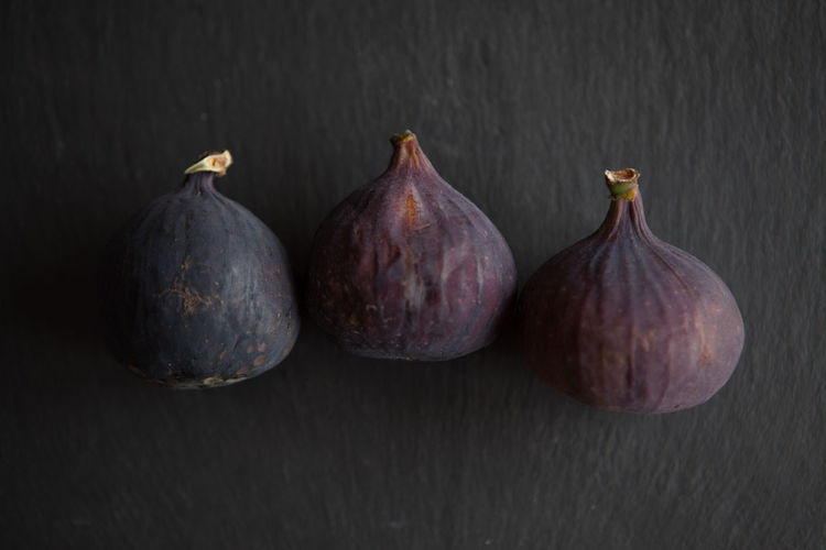 Beautiful fresh blue violet figs on dark stone background with empty copyspace close up vie from above. Still Life Food And Drink Indoors  Wellbeing Freshness No People Food Healthy Eating Fig Close-up Studio Shot Table Group Of Objects Fruit Three Objects Black Background Wood - Material Side By Side Directly Above Five Objects Purple