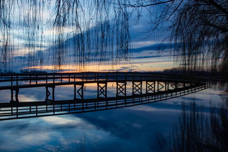 Silhouette bridge over lake against sky during sunset