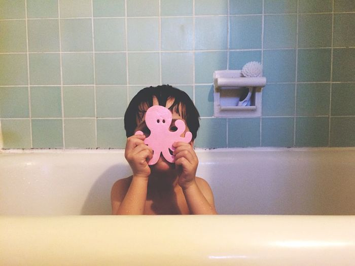 Boy with toy taking bath in tub at home