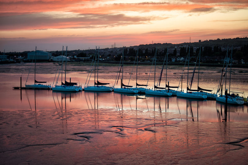 Sailboats Moored In River Against Sky During Sunset