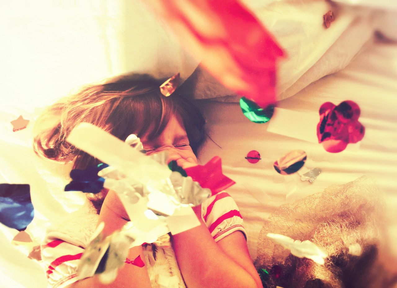 Girl lying on bed tossing confetti and laughing