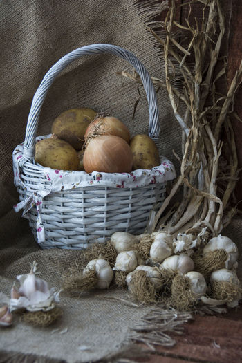 Close-up of potatoes and onions in basket by garlics on table