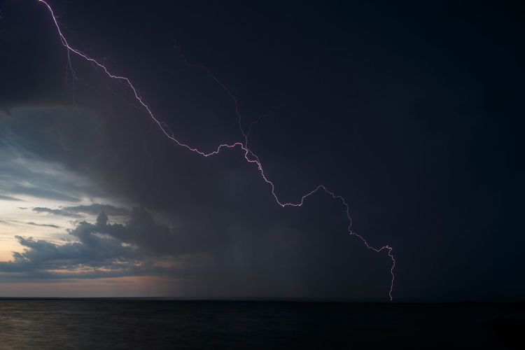 Forked lightning over sea against sky at night