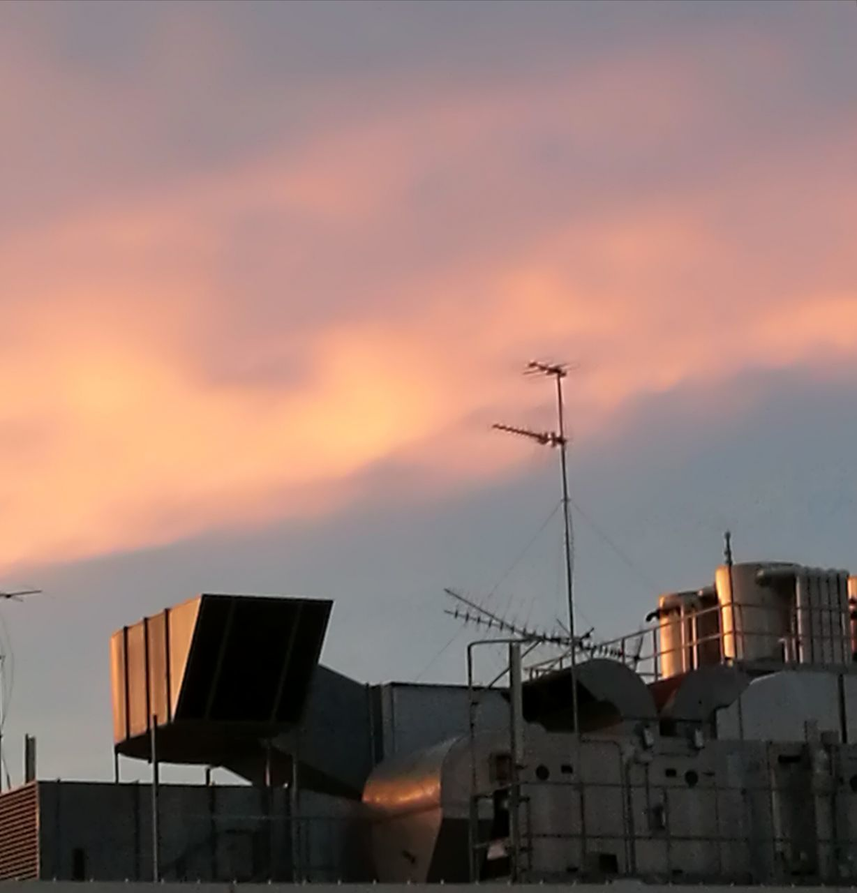 sunset, architecture, building exterior, sky, built structure, cloud - sky, orange color, nature, building, no people, communication, residential district, roof, antenna - aerial, outdoors, city, low angle view, television aerial, silhouette, technology, construction equipment