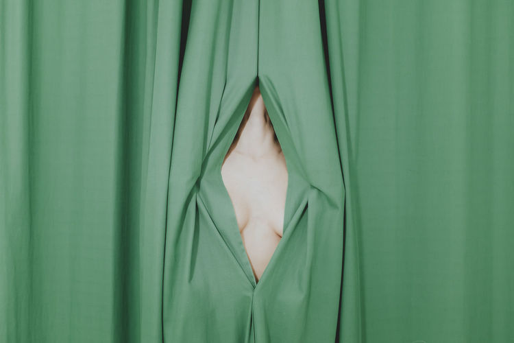 Close-up of a woman hiding behind curtain
