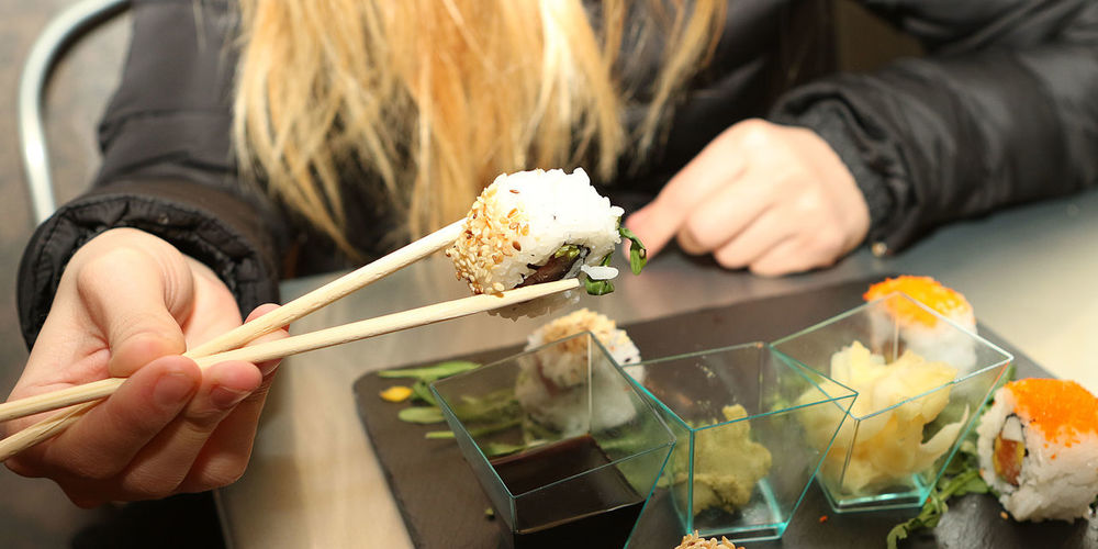 Cropped image of woman eating sushi at restaurant