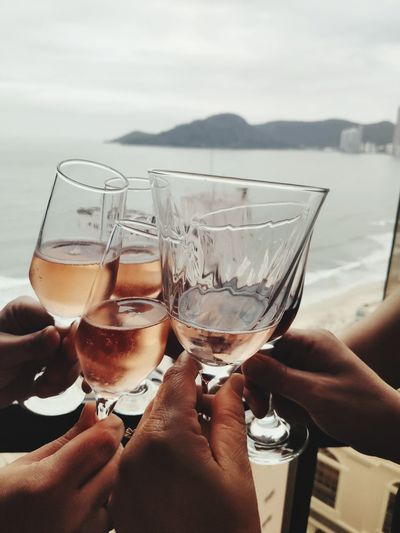 Midsection of persons holding rose wine in glass